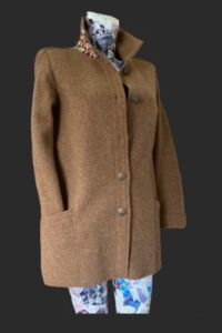 Loose fitting jacket with tweed trim collar, pockets in sleeve and patch pockets.
