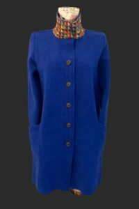 Loose fitting a line coat with brass buttons and Aztec trim on collar.