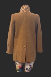 Back view showing the low split with a button trim